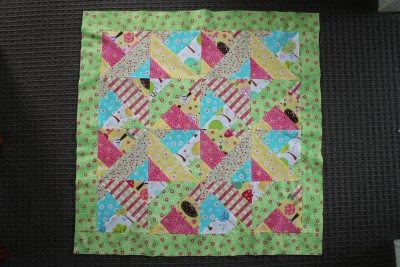 On this blanket I chose the green with little pink flowers for the first border. Sew on the top and bottom first and then the edges. Make sure to slightly stretch the material as you sew. This makes it easier for the quilt to keep shape, and for the top stitching later on.